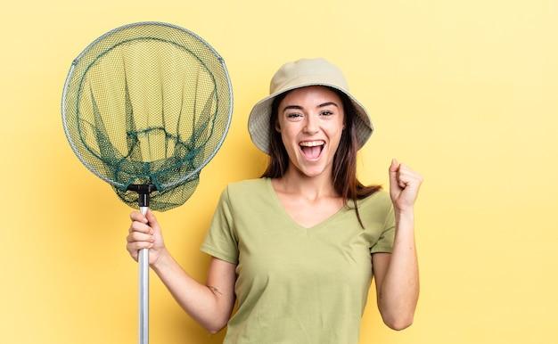Młoda latynoska kobieta czuje się zszokowana, śmieje się i świętuje sukces koncepcji sieci rybnej