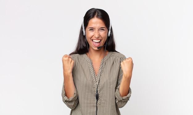 Młoda latynoska kobieta czuje się zszokowana, śmieje się i świętuje sukces za pomocą zestawu słuchawkowego. koncepcja telemarketingu