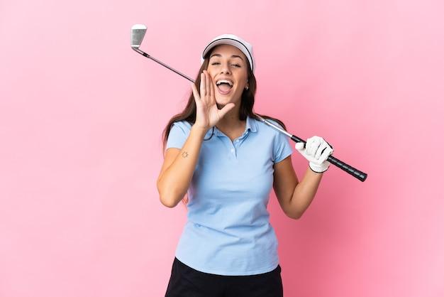 Młoda latynoska kobieta grająca w golfa na różowym tle i krzycząca z szeroko otwartymi ustami