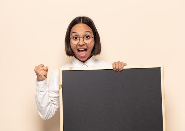 Młoda latynoska kobieta jest zszokowana, podekscytowana i szczęśliwa
