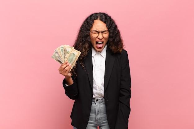 """Młoda latynoska kobieta krzycząca agresywnie, wyglądająca na bardzo rozgniewaną, sfrustrowaną, oburzoną lub zirytowaną, krzyczącą """"nie"""". koncepcja banknotów dolarowych"""