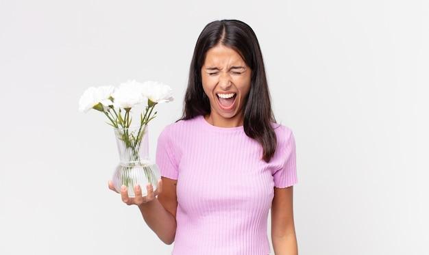 Młoda latynoska kobieta krzycząca agresywnie, wyglądająca na bardzo rozgniewaną, trzymająca ozdobne kwiaty