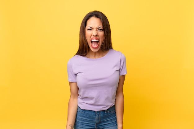 Młoda latynoska kobieta krzycząca agresywnie, wyglądająca na bardzo rozgniewaną