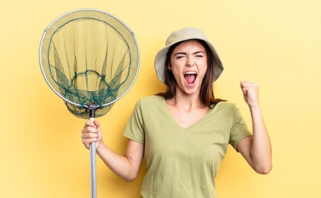 Młoda latynoska kobieta krzycząca agresywnie z gniewnym wyrazem koncepcji sieci rybackiej