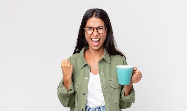 Młoda latynoska kobieta krzycząca agresywnie z gniewnym wyrazem twarzy i trzymająca kubek z kawą