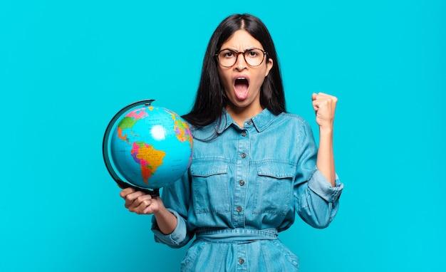 Młoda latynoska kobieta krzycząca agresywnie z gniewnym wyrazem twarzy lub z zaciśniętymi pięściami świętuje sukces. koncepcja planety ziemi