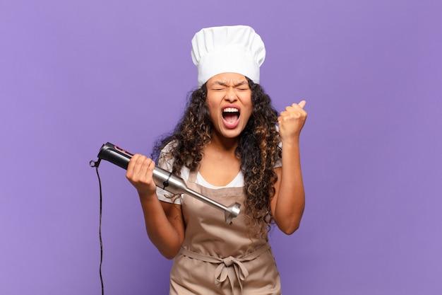 Młoda latynoska kobieta krzycząca agresywnie z gniewnym wyrazem twarzy lub z zaciśniętymi pięściami świętuje sukces. koncepcja szefa kuchni