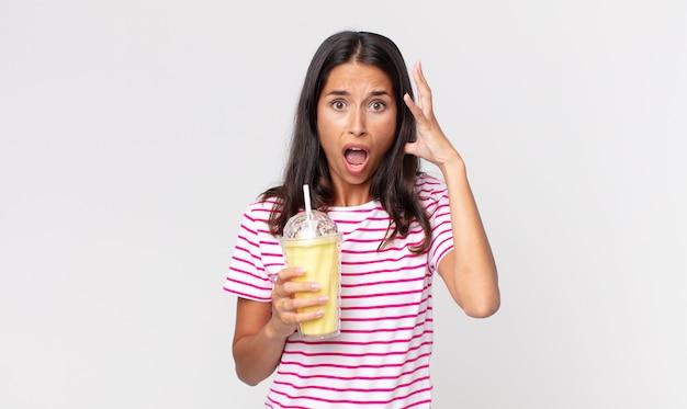 Młoda latynoska kobieta krzycząca z rękami w górze i trzymająca koktajl mleczny o smaku waniliowym