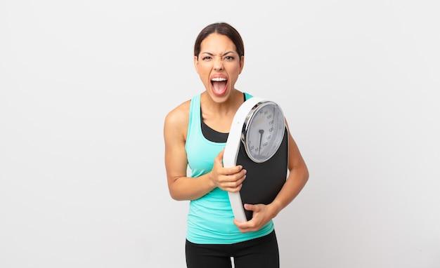 Młoda latynoska kobieta krzyczy agresywnie, wygląda na bardzo rozgniewaną i trzyma wagę