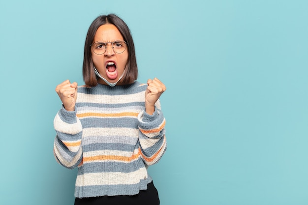 Młoda latynoska kobieta krzyczy agresywnie z gniewnym wyrazem twarzy lub z zaciśniętymi pięściami świętując sukces