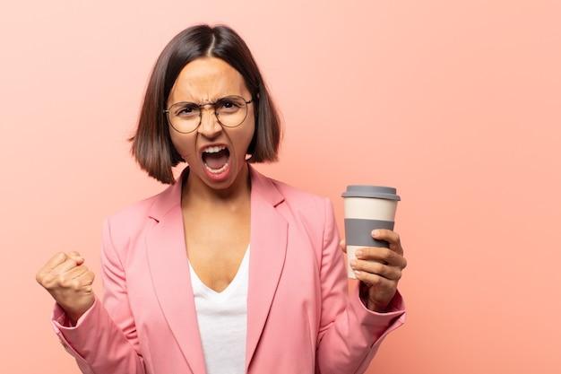 Młoda latynoska kobieta krzyczy agresywnie z gniewnym wyrazem twarzy lub z zaciśniętymi pięściami świętuje sukces