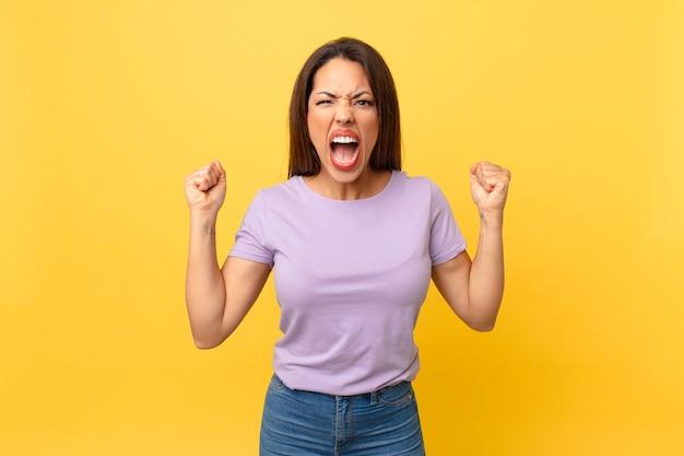 Młoda latynoska kobieta krzyczy agresywnie z gniewnym wyrazem twarzy
