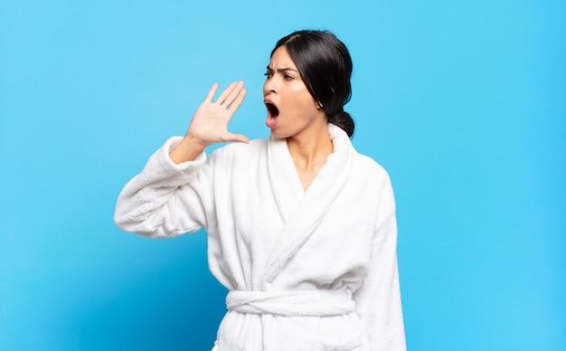 Młoda latynoska kobieta krzyczy głośno i ze złością, aby skopiować miejsce z boku, z ręką przy ustach. koncepcja szlafrok