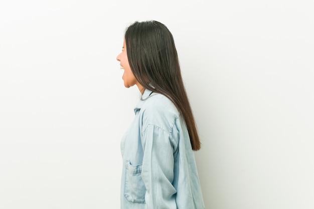 Młoda latynoska kobieta krzyczy w kierunku odbitkowej przestrzeni