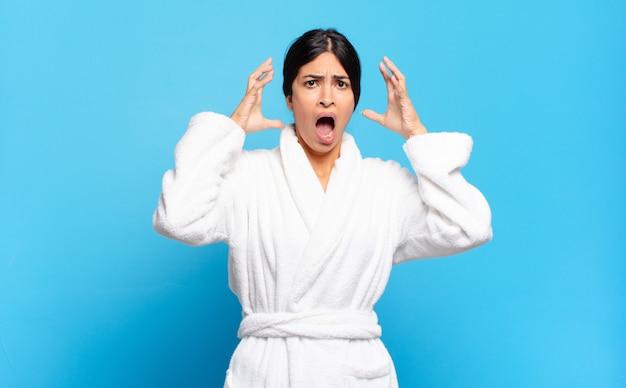 Młoda latynoska kobieta krzyczy z rękami do góry, czuje się wściekła, sfrustrowana, zestresowana i zdenerwowana