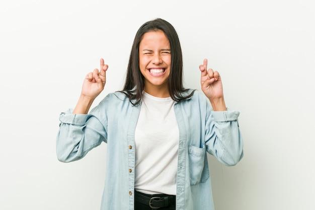 Młoda latynoska kobieta krzyżuje palce za mieć szczęście