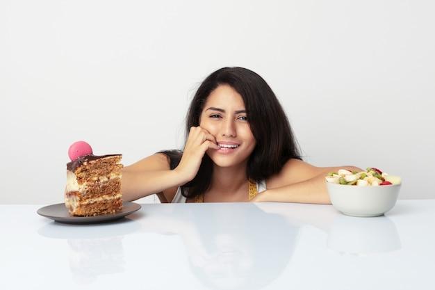 Młoda latynoska kobieta, która wybiera między tortem a owocami obgryzającymi paznokcie, nerwowa i bardzo niespokojna.