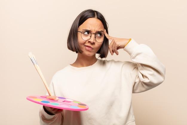 Młoda latynoska kobieta, która wygląda na skoncentrowaną i intensywnie myśli o pomyśle, wyobrażając sobie rozwiązanie wyzwania lub problemu
