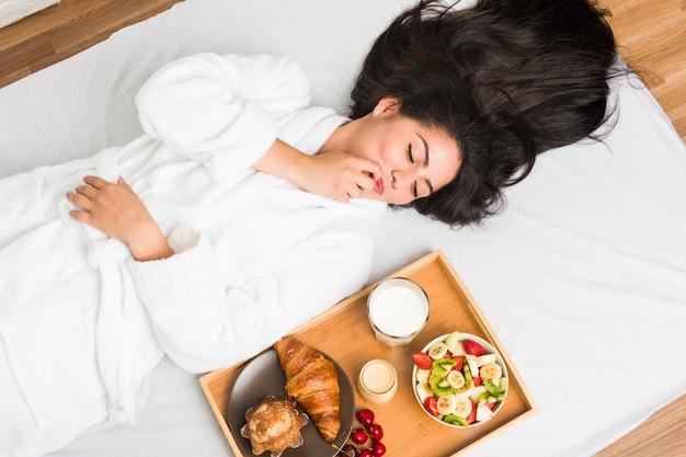 Młoda latynoska kobieta ma śniadanie na łóżku