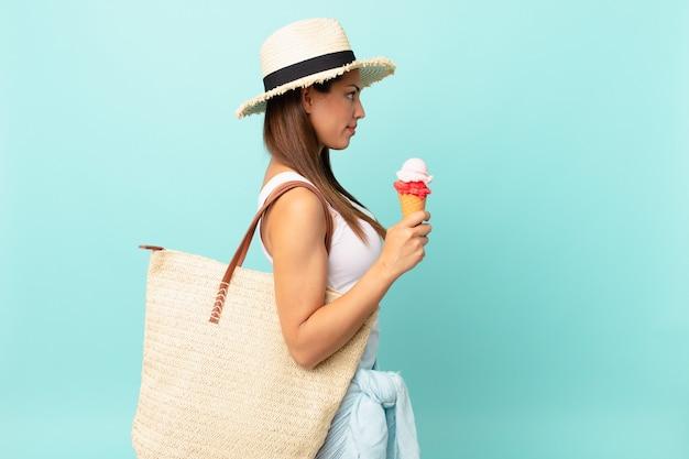 Młoda latynoska kobieta myśląca, wyobrażająca sobie lub marząca o widoku profilu i trzymająca lody. koncepcja suma