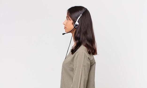 Młoda latynoska kobieta myśląca, wyobrażająca sobie lub marząca o widoku profilu za pomocą zestawu słuchawkowego. koncepcja telemarketingu