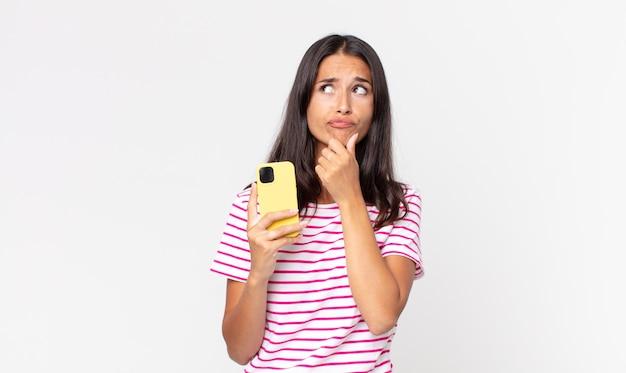 Młoda latynoska kobieta myśli, czuje się zwątpienie i zdezorientowana i trzyma smartfona
