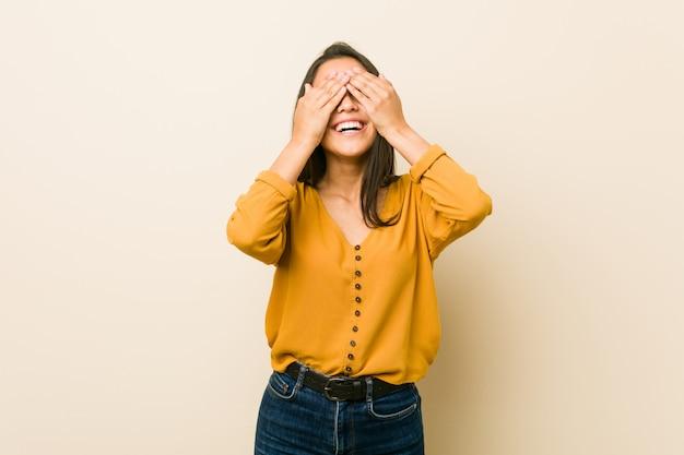 Młoda latynoska kobieta na beżowej ścianie zakrywa oczy dłońmi, uśmiecha się szeroko, czekając na niespodziankę.