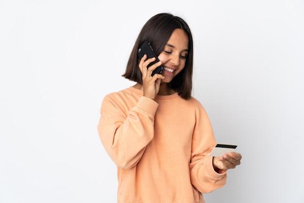 Młoda latynoska kobieta na białym tle kupując za pomocą telefonu komórkowego za pomocą karty kredytowej
