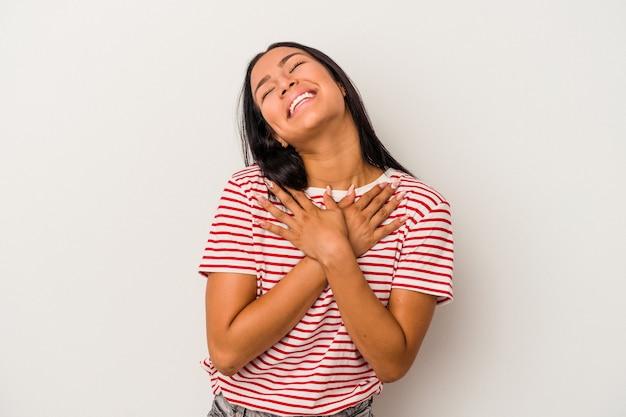 Młoda latynoska kobieta na białym tle ma przyjazny wyraz, przyciskając dłoń do klatki piersiowej. koncepcja miłości.