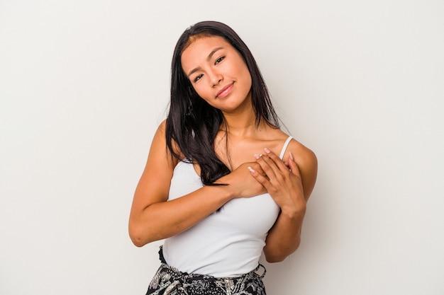 Młoda latynoska kobieta na białym tle ma przyjazny wyraz twarzy, przyciskając dłoń do klatki piersiowej. koncepcja miłości.