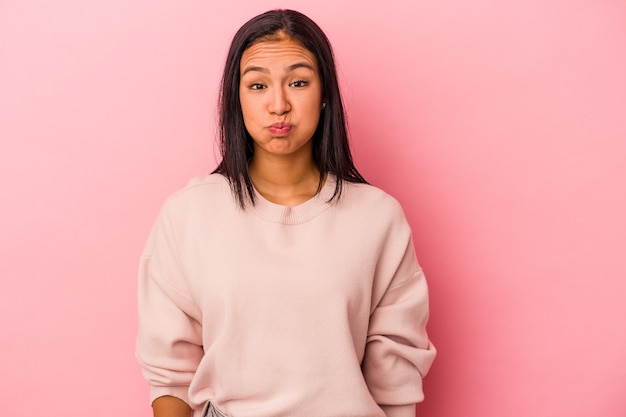 Młoda latynoska kobieta na białym tle na różowym tle dmucha w policzki, ma zmęczony wyraz twarzy. koncepcja wyraz twarzy.