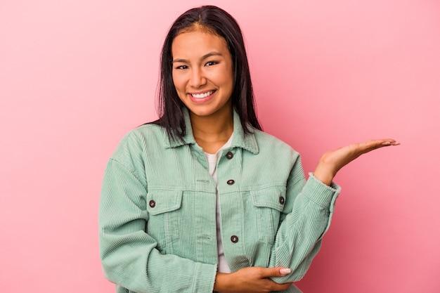 Młoda latynoska kobieta na białym tle na różowym tle pokazująca miejsce na dłoni i trzymająca drugą rękę na pasie.