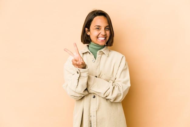 Młoda latynoska kobieta na białym tle radosny i beztroski pokazując palcami symbol pokoju.