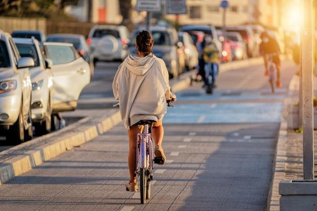 Młoda latynoska kobieta na rowerze na trasie rowerowej o piękny zachód słońca