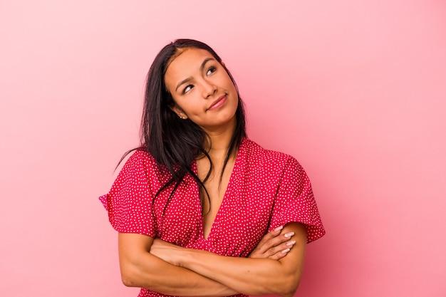 Młoda latynoska kobieta na różowym tle marząca o osiągnięciu celów i celów