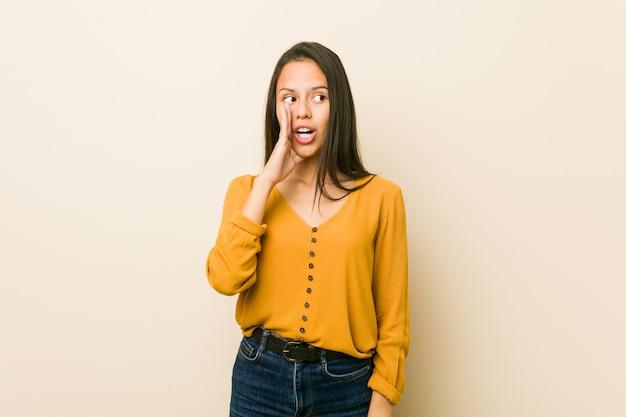 Młoda latynoska kobieta o beżowej ścianie mówi tajemniczą gorącą wiadomość o hamowaniu i patrzy na bok