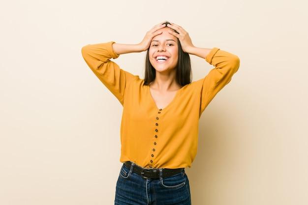 Młoda latynoska kobieta o beżowej ścianie śmieje się z radości trzymając się za ręce. koncepcja szczęścia.
