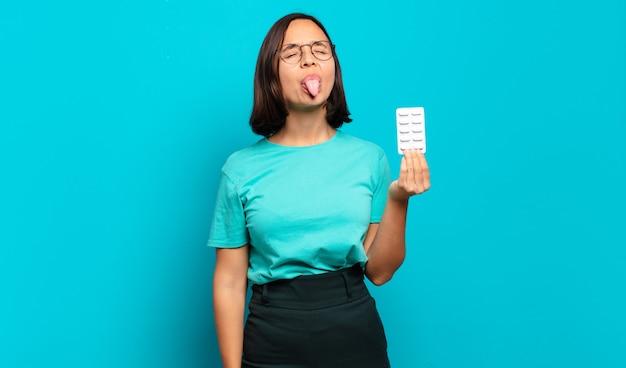 Młoda latynoska kobieta o pogodnym, beztroskim, buntowniczym nastawieniu, żartuje i wystawia język, dobrze się bawi
