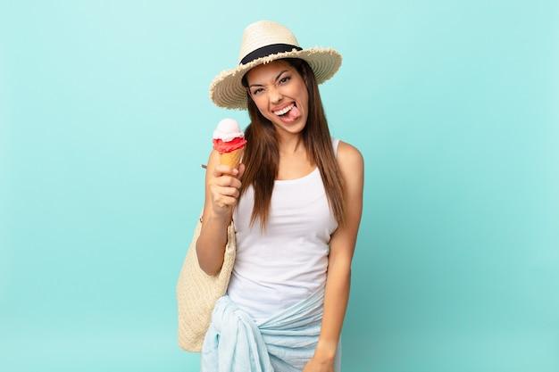 Młoda latynoska kobieta o radosnym i buntowniczym nastawieniu, żartująca, wystawiająca język i trzymająca lody. koncepcja suma