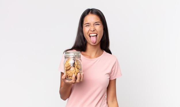Młoda latynoska kobieta o radosnym i buntowniczym nastawieniu, żartująca, wystawiająca język i trzymająca szklaną butelkę po ciastkach