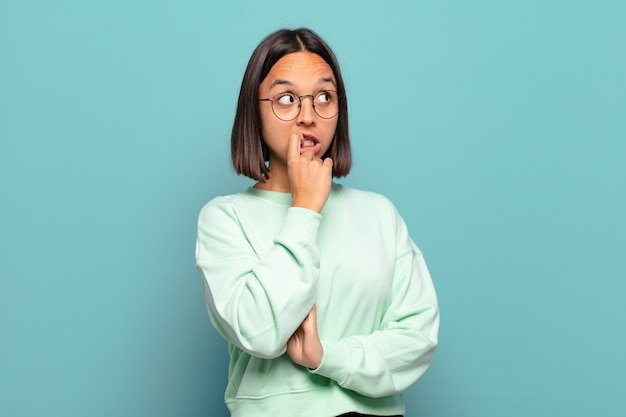 Młoda latynoska kobieta o zdziwionym, nerwowym, zmartwionym lub przestraszonym spojrzeniu, patrząca w bok w kierunku miejsca kopiowania