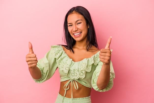Młoda latynoska kobieta odizolowana na różowym tle uśmiecha się i podnosi kciuk w górę