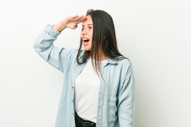 Młoda latynoska kobieta patrzeje daleki utrzymuje rękę na czole.