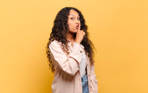 """Młoda latynoska kobieta prosi o ciszę i spokój, gestykuluje palcem przed ustami, mówi """"cii"""" lub dochowuje tajemnicy"""