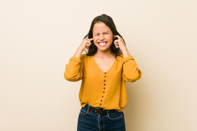 Młoda latynoska kobieta przeciw beżowej ścianie zakrywającej ucho z rękami.