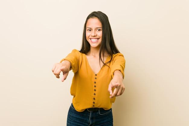 Młoda latynoska kobieta przeciw beżowemu tłu wesoło uśmiecha się wskazywać