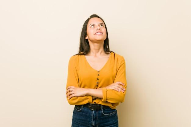 Młoda latynoska kobieta przy beżowej ścianie zmęczona powtarzającym się zadaniem.