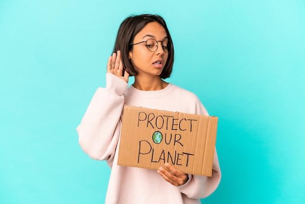 Młoda latynoska kobieta rasy mieszanej trzymająca karton chroniący naszą planetę, próbująca słuchać plotek.