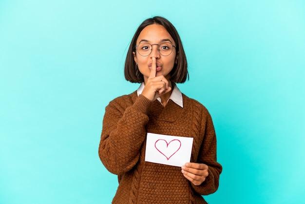 Młoda latynoska kobieta rasy mieszanej trzymająca papier serca trzymająca w tajemnicy lub prosząca o ciszę.