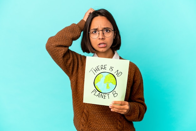 Młoda latynoska kobieta rasy mieszanej trzymająca tabliczkę z informacją o ochronie planety, będąc zszokowana, przypomniała sobie ważne spotkanie